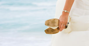 Bride with shoes in hands. Bride looking at the sea with shoes in hands Royalty Free Stock Photography