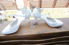 Bride shoes on wooden railing Stock Photos