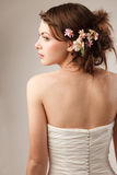 Bride shooted from back. Modern bride with flowers in her hair looking away royalty free stock photo