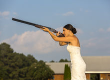 Bride with Shotgun. A bride in a wedding dress shooting a shotgun Stock Images