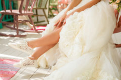 Bride show her legs in funny wedding shoes Stock Image