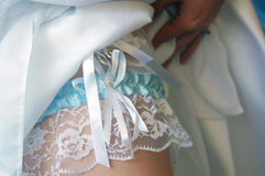 Bride showing garter on leg. Close up of bride lifting dress up to show garter on leg Royalty Free Stock Photos