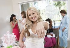 Bride Showing Her Engagement Ring At Hen Party. Portrait of a beautiful young bride showing her engagement ring with friends in the background Stock Image