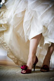 Bride showing off her red high heel shoes Stock Photos