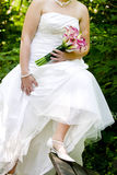 Bride showing off wedding dress and shoes Stock Photo