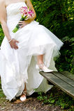 Bride showing off wedding dress and shoes Stock Photos