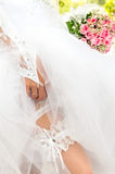 The bride shows the garter on her leg Royalty Free Stock Photography