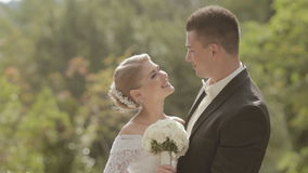Bride shows language to groom and kissing him stock video footage