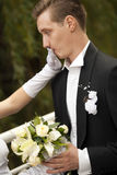 Bride shutting groom's mouth. Colorful wedding shot of bride shutting groom's mouth stock photo