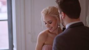 Bride shyly turned away from the groom. The bride and groom exchange rings at a wedding ceremony in the studio on a background of beautiful flowers. Wedding in stock footage