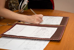 Bride Signing Marriage Certificate. Photo of bride signing the marriage certificate Stock Photo