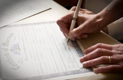 Bride signing marriage license. Bride signs the marriage certificate with ring on hand Stock Image