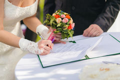 Bride signing marriage license Stock Photo