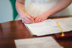 Bride signing marriage license Royalty Free Stock Photo