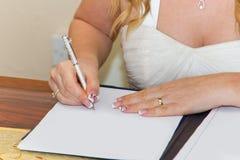 Bride signing marriage registration form. Married couple signing marriage registration form Stock Photos