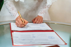 Bride signing signature on wedding certificate Stock Photo