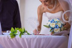Bride signing wedding certificate in park Stock Image