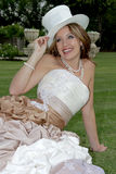 Bride Sit. A bride sitting on grass holding a hat Royalty Free Stock Photography