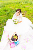 Bride sit on a grass with a big basket with fruit Stock Photography