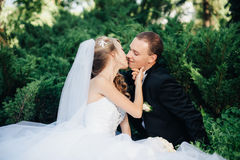 Bride sit together with groom on green grass park Royalty Free Stock Photos