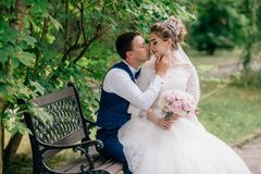 The bride sits in the arms of her fiance, who gently holds her chin and turns to him for a kiss. Happy newlyweds enjoy a royalty free stock photo