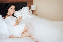 The bride sits on the bed and keeps the wedding dress in the hands Royalty Free Stock Images