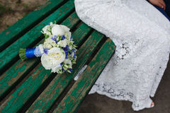 The bride sits on a bench next to wedding bouquet Royalty Free Stock Photo