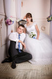 The bride sits in a chair and the groom sits near bride on the floor in the room royalty free stock images