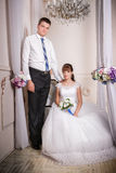 The bride sits in a chair and the groom stands near bride in the room stock photography