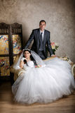 Bride sits in a chair and the groom stands near groom in the room with a beautiful interior Stock Images