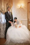 Bride sits in a chair and the groom stands near groom in the room stock photos