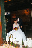 Bride sits on a chair in an old restaurant while groom kisses he royalty free stock photos