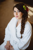 Bride sits on a chair in white robe Stock Images