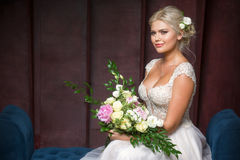 Bride sits on a couch and holding a bouquet. Of flowers Royalty Free Stock Image