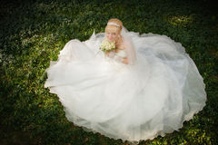 Bride sits on a green grass Royalty Free Stock Photography