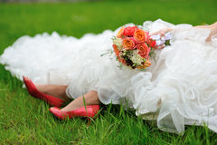 Bride sits on green lawn. Bride on the green lawn with bouquet and red shoes Stock Photography