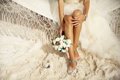 Tropical wedding. Bride on the beach, feet of the bride, wedding bouquet royalty free stock image