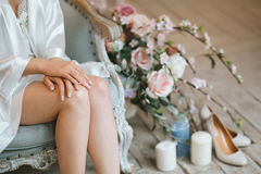 Bride sits in the morning on a vintage blue chair dressed in a silk dressing gown Stock Photos
