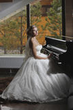 The bride sits at the piano Royalty Free Stock Photos