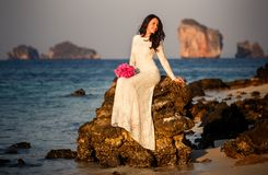 bride sits on rock at beach at sunrise Royalty Free Stock Photo