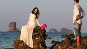 Bride sits on rock and groom comes at sunrise stock video footage