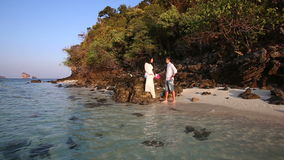 Bride sits on rock and groom comes to her at sunrise stock footage