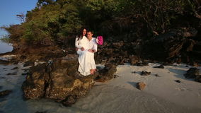 Bride sits on rock and groom holds hands at sunrise stock video footage
