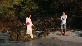 Bride sits on rock  and groom looks from beach at sunrise stock footage