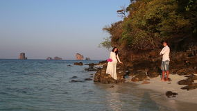 Bride sits on rock and groom looks from beach at sunrise stock video