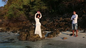 Bride sits on rock and lifts bouquet stock footage