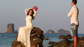 Bride sits on rock and poses groom looks at sunrise stock video