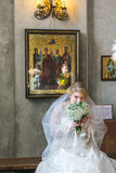Bride sits and and smells flowers. MOSCOW - MARCH 10: bride sits and and smells flowers during orthodox wedding ceremony on March 10, 2013 in Moscow Stock Images
