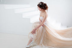 Bride sits on the stairs. Portrait of a beautiful girl in a wedding dress. Dancing Bride, white background. Royalty Free Stock Photography