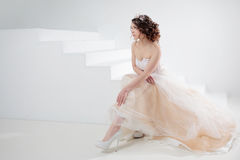 Bride sits on the stairs. Portrait of a beautiful girl in a wedding dress. Dancing Bride, white background. Stock Image